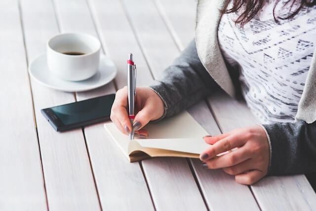 امرأة تكتب في مفكرة مع فنجان قهوة